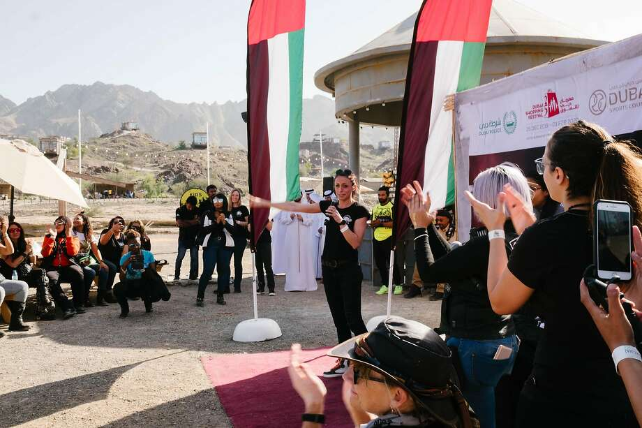 Hayley Bell, the founder of the Women Riders World Relay, speaks in Hatta, an area in the mountains of Dubai. More than 3,500 women from 79 countries participated in the relay. Below: Riders head to Hatta. Photo: Photos By Anna Nielsen / New York Times