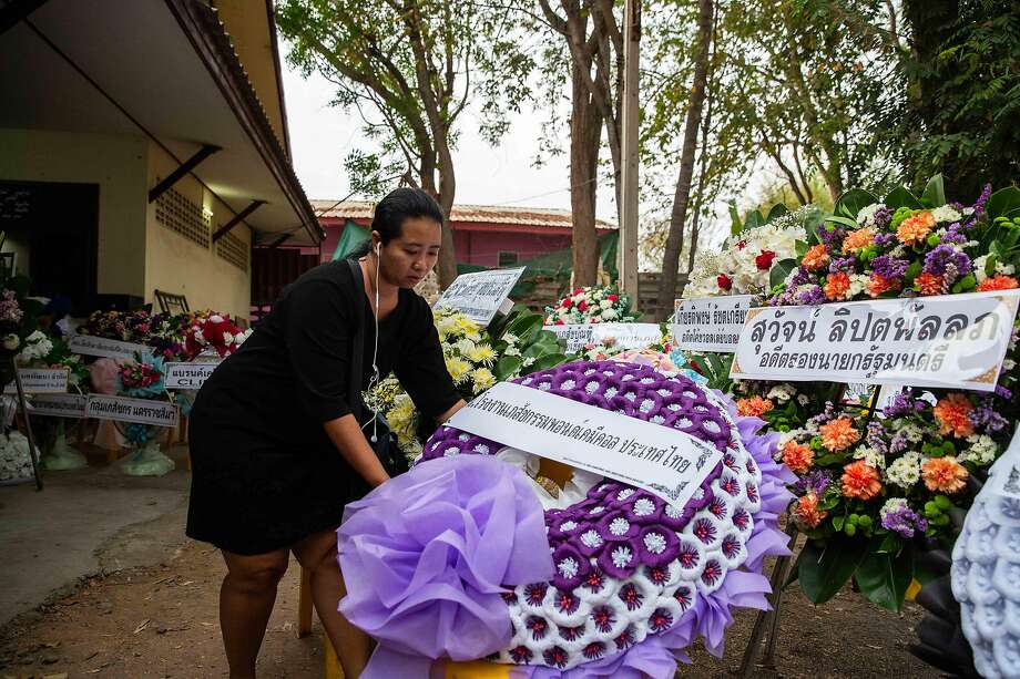 A mourner places a flower arrangement at a funeral for shooting victims in the town of Korat. Photo: Lauren DeCicca / Getty Images