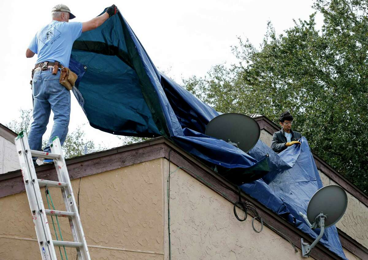 Volunteers work to cover the roof of a home in the Westbranch neighborhood to prevent further damage by the projected rain Saturday, Jan. 25, 2020, in Houston. Many homes in the neighborhood were severely damaged by the explosion at Watson Grinding and Manufacturing.
