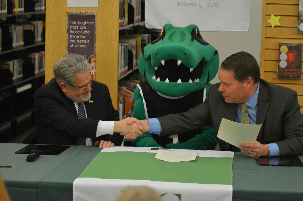 Sage President Christopher Ames shakes hands with East Greenbush Central School District Superintendent Jeffrey Simons during their announcement of an Early Assurance Agreement between the two schools.