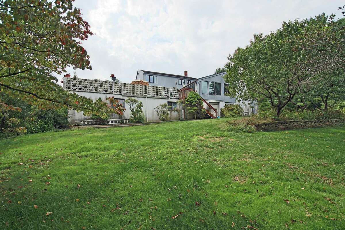 The house sits on a three-acre level property with fruit trees and a vegetable garden.