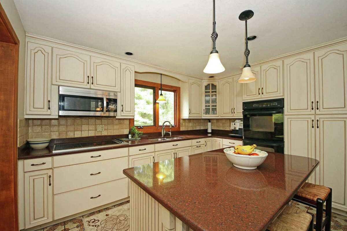 In the eat-in kitchen there is a center island with a breakfast bar, granite counters, double stainless sinks, ample cabinets, and a large breakfast or casual dining area.