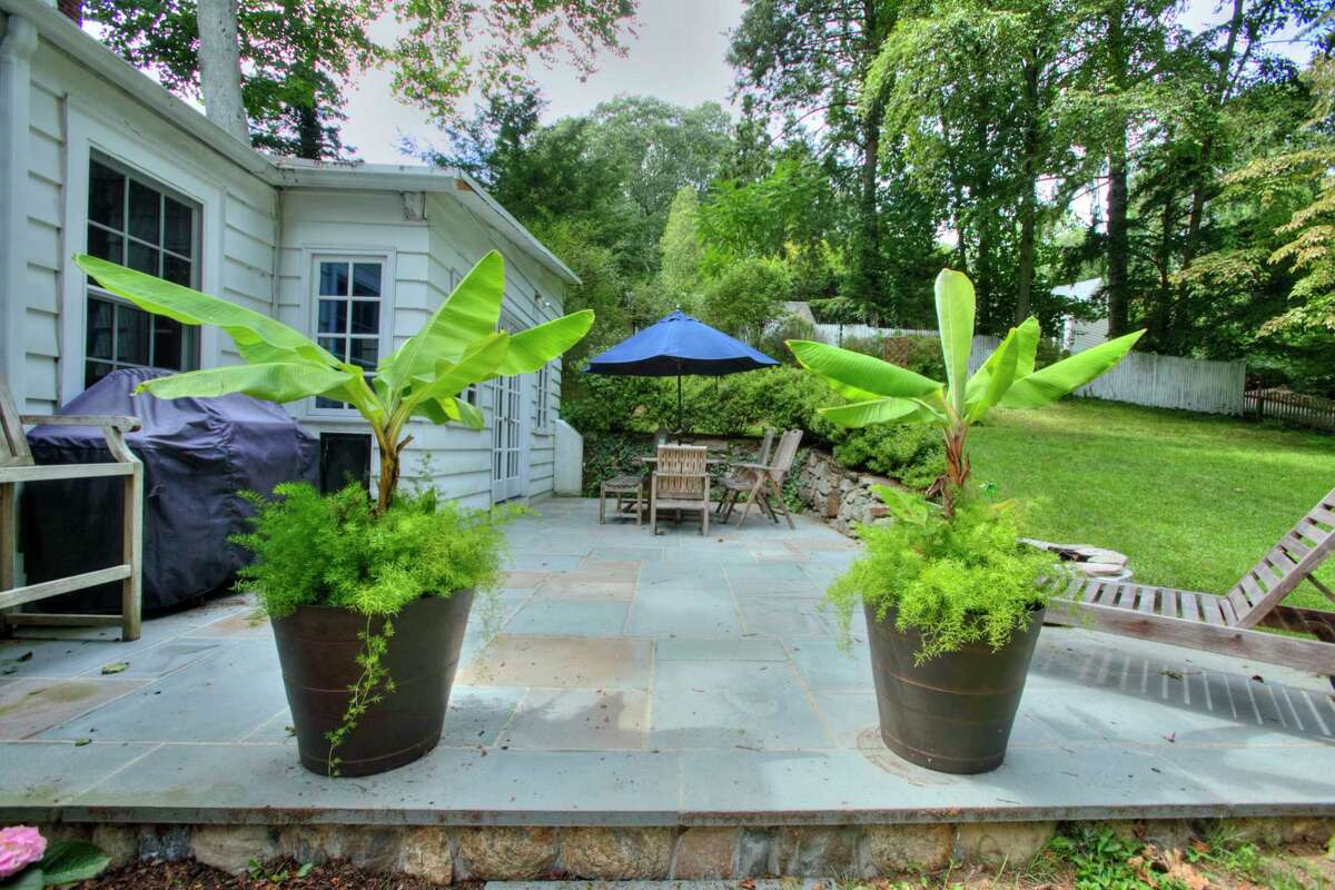 In the private, fenced backyard there is a slate patio, a fire pit, and a playhouse.