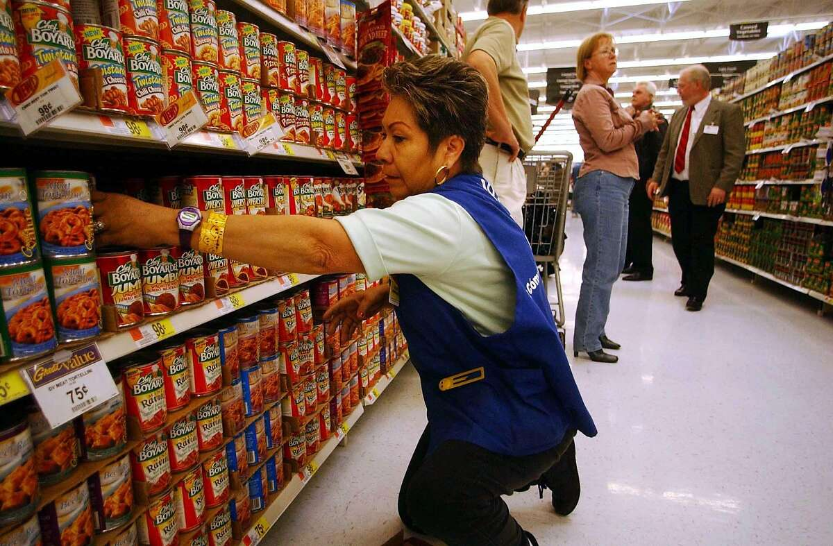 Employee Maria Banuelos stocks shelves at the grand opening of the Wal-Mart SuperCenter in La Quinta, California, March 3, 2004. The 225,000 square-foot store in La Quinta, California, is the first of about 40 so-called supercenters Wal-Mart plans to open in California over the next four years. By adding low-priced milk, meat and fruit to its stores, Wal-Mart has lured away shoppers from supermarkets to become the largest grocer in the U.S. Photographer: Sandy Huffaker /Bloomberg News.