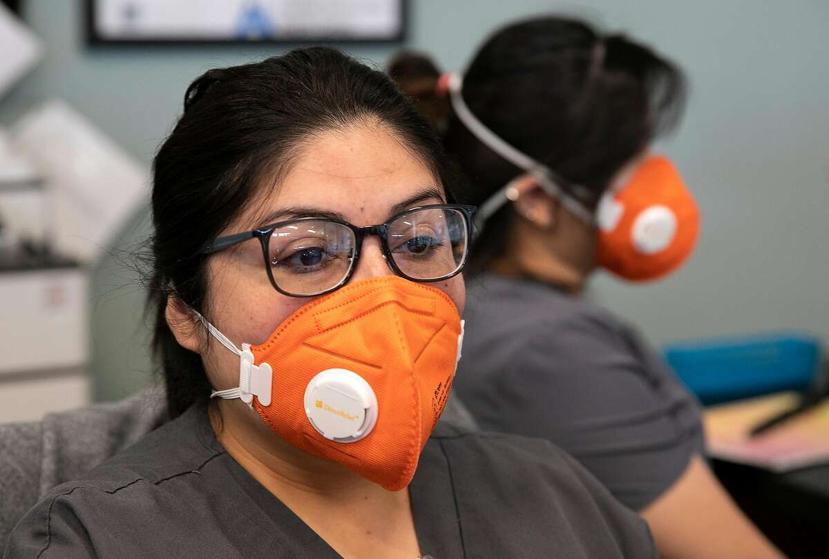 From left, Dental Clinic Manager Elena Blanco and Front Desk Dental Receptionist Han Vu wear N95 masks while manning the front desk at the Foothill Community Health Center on Monday, Feb. 10, 2020 in San Jose, Calif.