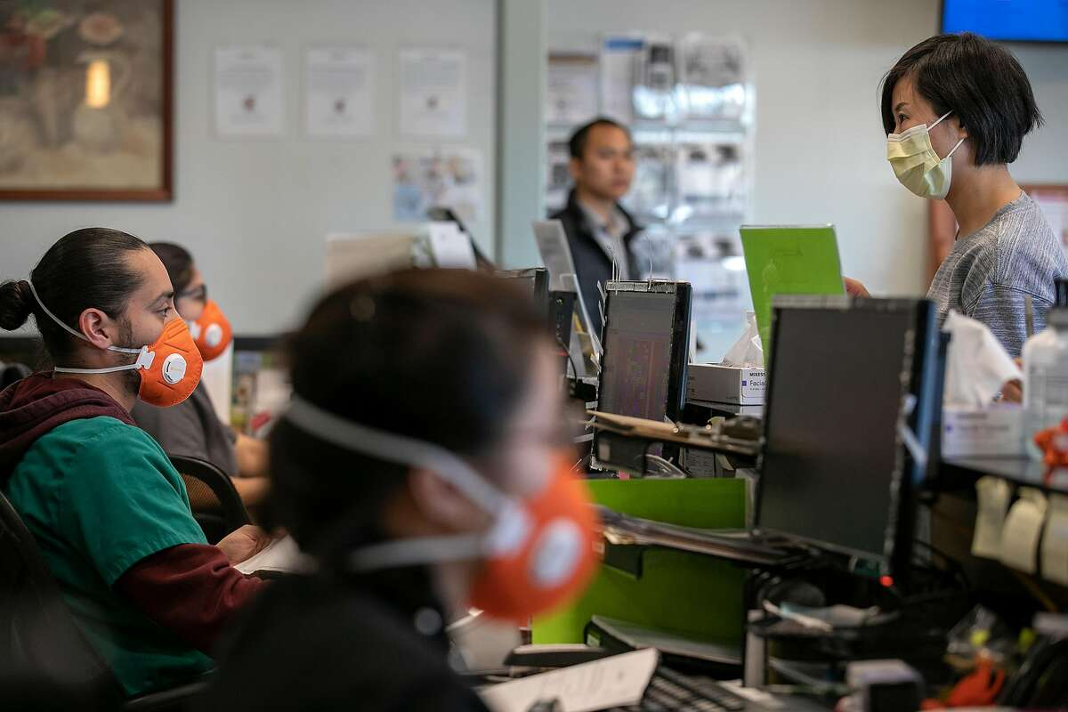 Wearing an N95 face mask, Front Medical Assistant Lead Edwin Moreno, left, helps Jessica Yu, of San Jose, right, at the Foothill Community Health Center on Monday, Feb. 10, 2020 in San Jose, Calif.