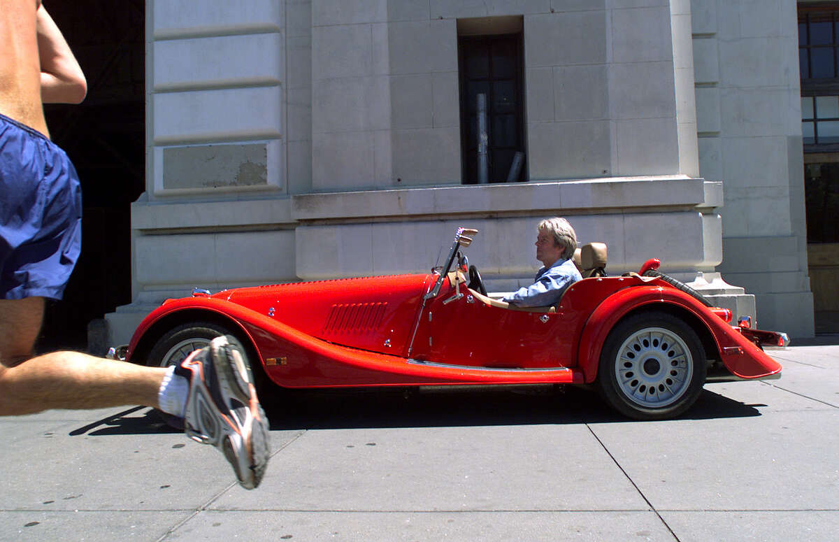 FILE - A jogger on the Embarcadero runs past Bill Fink and his Morgan about to enter his Pier 33 garage in 2000.