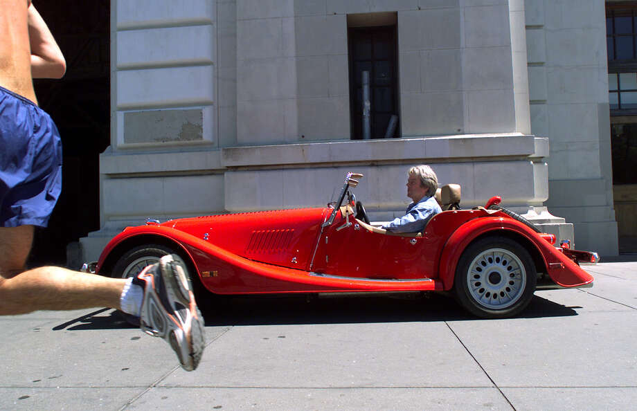 FILE - A jogger on the Embarcadero runs past Bill Fink and his Morgan about to enter his Pier 33 garage in 2000. Photo: Brant Ward, Hearst