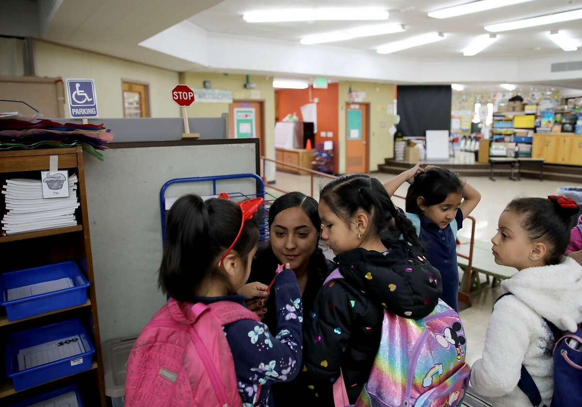 Jasmine Gonzalez, a kindergarten and first grade after school instructor, listens to Yumine Hermosillo Teodoro, 5, a kindergartener, left, while standing beside Mina Gomez, 5, also a kindergartener, at Lake Elementary School, located at 2700 11th St., in San Pablo, Calif., on Thursday, February 6, 2020. In this area of the school, the classrooms don't have walls to provide division. Prop. 13 would authorize a $15 billion bond for school facilities.