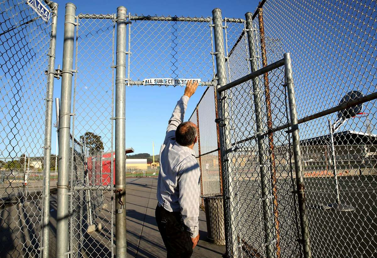 Principal Jose De Leon straightens a sign at Richmond High School, located at 1250 23rd St., in Richmond, Calif., on Thursday, February 6, 2020. Prop. 13 would authorize a $15 billion bond for school facilities.