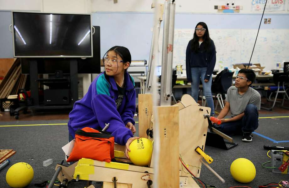 Pasang Sherpa (left) sets a ball for launch from a a robot as Salma Gamez and Jesus Mora watch in the robotics lab at Richmond High School. The school's lab needs an electrical upgrade. Photo: Photos By Yalonda M. James / The Chronicle
