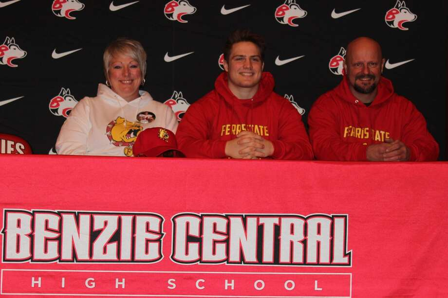 Cody Hanson, flanked by his parents Amy Hanson and Chad Hanson, signs his letter of intent to play football at Ferris State University. Photo: Robert Myers