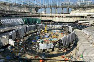 Workers work on the interior of SoFi Stadium and prepare to raise the circular Oculus video board in Inglewood, Calif., on Wednesday, Jan. 22, 2020. The estimated $5 billion project is on schedule to open in July as the most expensive stadium in NFL history. WWE has announced that it will hold WrestleMania 37 at the stadium on March 28, 2021.