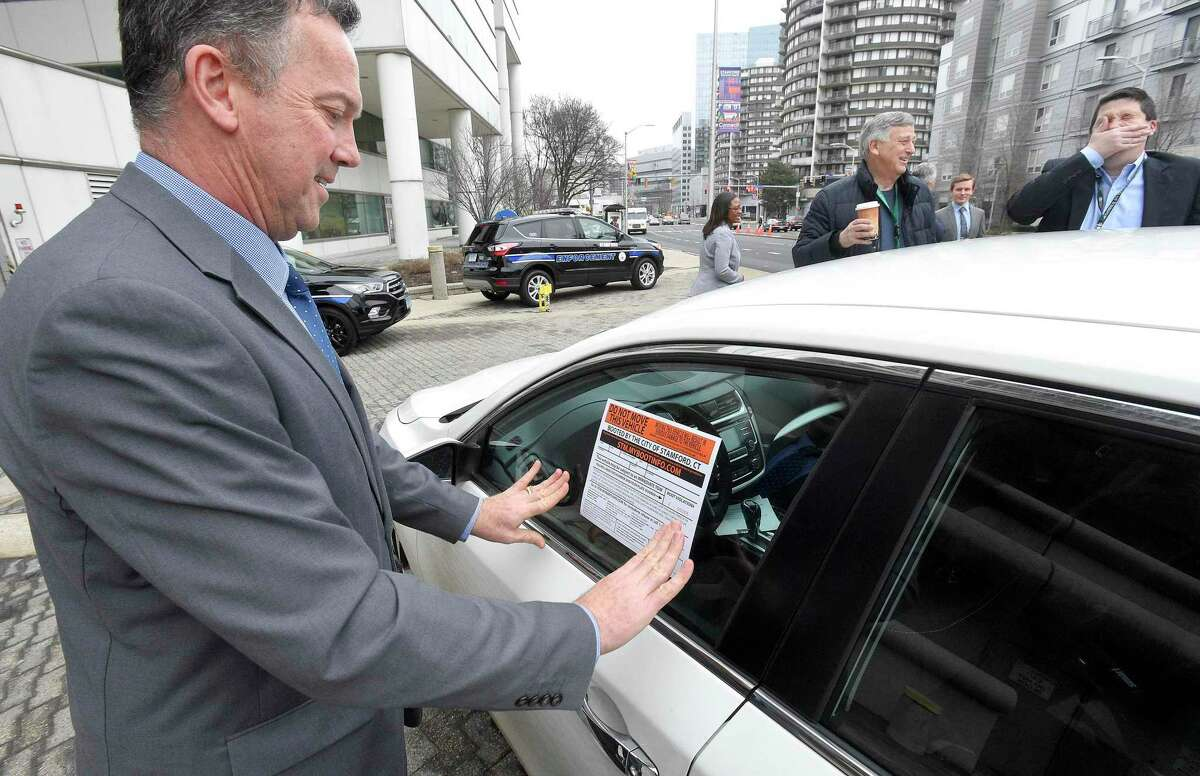 Transportation Bureau Chief Jim Travers places a sticker onto a window that notifies the owner that their vehicle has been disabled with the new self-releasing electronic boot on Feb. 7in Stamford.