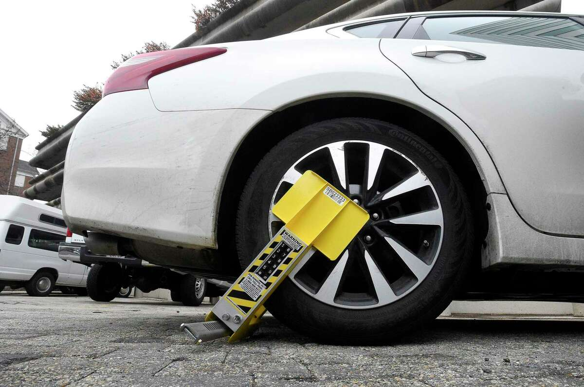 A vehicle is disabled with a new self-releasing electronic boot on Thursday, Feb. 7, 2019 in Stamford, Connecticut. The city has deployed the new boot device to go after almost 5,700 scofflaws in Stamford who have about 28,000 parking tickets and owe the city almost $2.1 million.