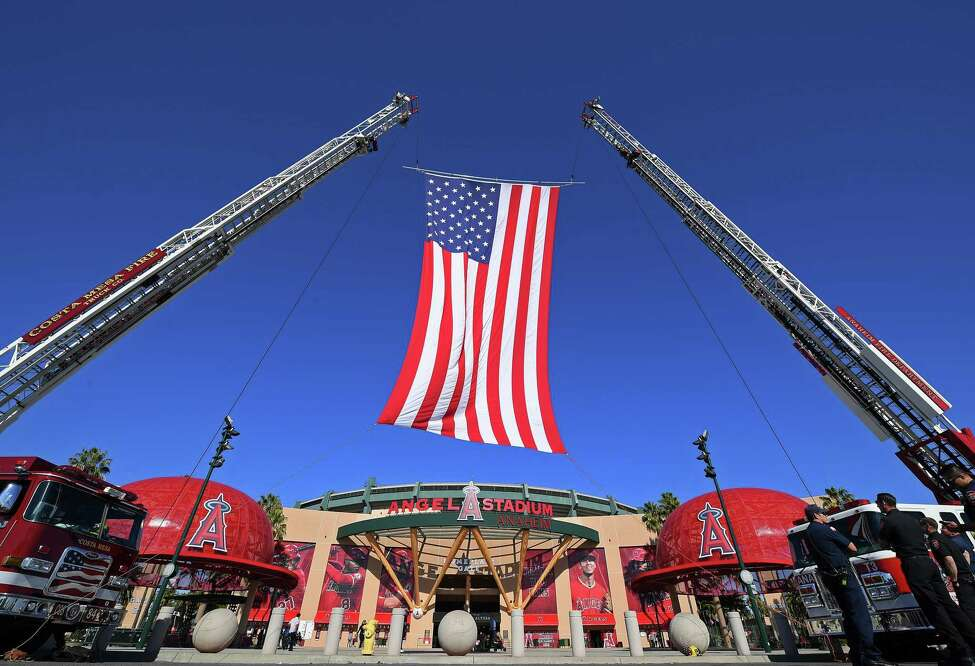 ANAHEIM, CA - FEBRUARY 10: The City of Anaheim fire department displays the America Flag as fans arrive for a memorial service honoring baseball coach John Altobelli, his wife, Keri, and their daughter Alyssa at Angel Stadium of Anaheim on February 10, 2020 in Anaheim, California. The Altobellis were traveling with former Lakers star Kobe Bryant, his 13-year-old daughter Gianna and four others when the helicopter crashed Jan. 26 in foggy conditions, killing everyone on board.