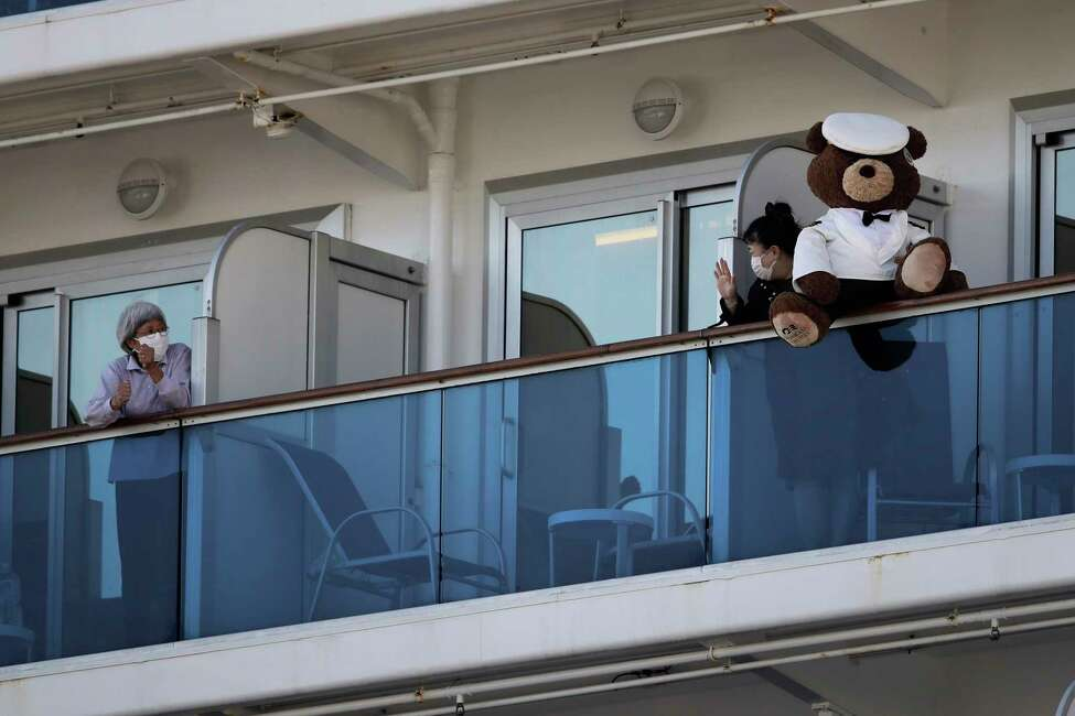 A woman with a teddy bear waves to another passenger quarantined on the Diamond Princess cruise ship in Yokohama, near Tokyo, Tuesday, Feb. 11, 2020. Japan's Health Minister Katsunobu Kato said the government was considering testing everyone remaining on board and crew on the Diamond Princess, which would require them to remain aboard until results were available. (AP Photo/Jae C. Hong)