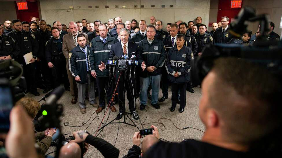 Patrolmen's Benevolent Association President Patrick J. Lynch, left, speaks with the media at the Bronx Criminal Court after NYPD Lt. Jose Gautreaux, who was shot in the arm by a gunman who opened fire in a police precinct in the Bronx, was released from Lincoln Hospital, Monday, Feb. 10, 2020, in New York. (AP Photo/Eduardo Munoz Alvarez)