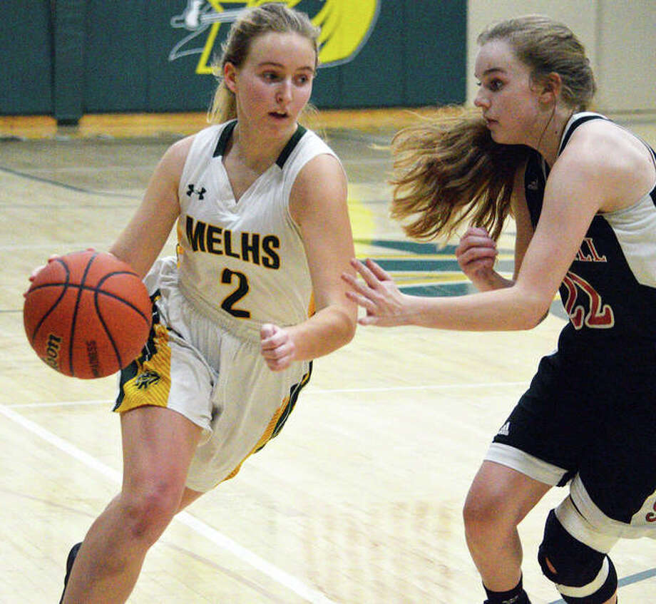 Metro-East Lutheran's Chloe Langendorf, left, drives to the basket during Monday's first-round game against Bunker Hill at the Class 1A MELHS Regional. Photo: Scott Marion/The Intelligencer