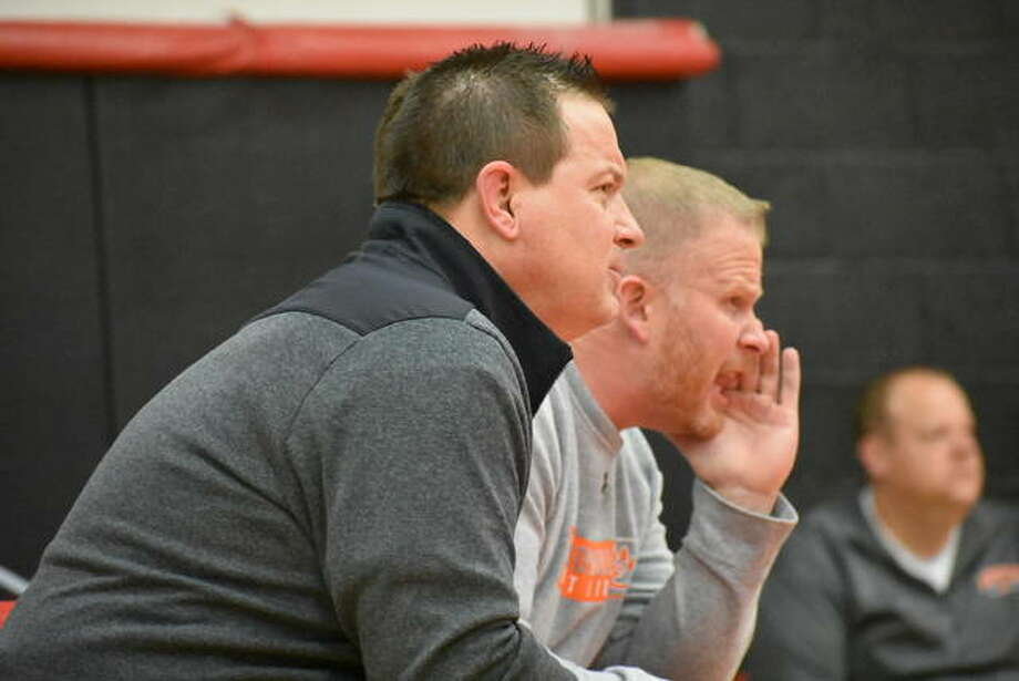 Edwardsville coach Jon Wagner, front, and assistant coach Doug Heinz watch on from the sideline during the regional championship match for heavyweight Lloyd Reynolds. Photo: Matt Kamp|The Intelligencer