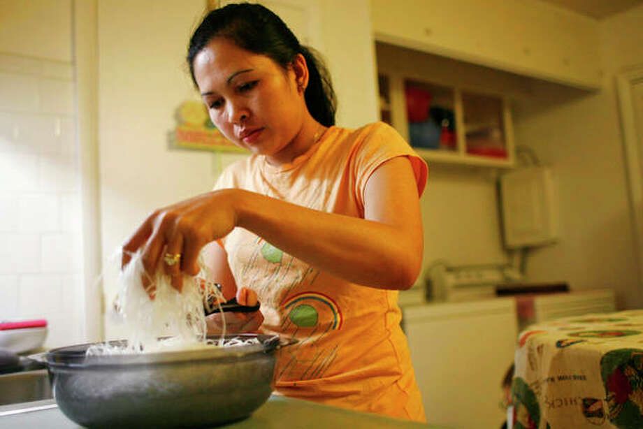 Elizabeth Keathley, a Philippine citizen in the U.S. on a marriage visa, cuts rice noodles as she prepares a traditional Filipino dish for dinner in Bloomington. She applied for a driver's license and was sent a voting registration card. She voted in 2006. In processing her green card, immigration authorities discovered she had voted, and she was ordered removed. However, judges determined she did not falsely represent herself, allowing her to stay. Photo: Abel Uribe | Chicago Tribune (AP)