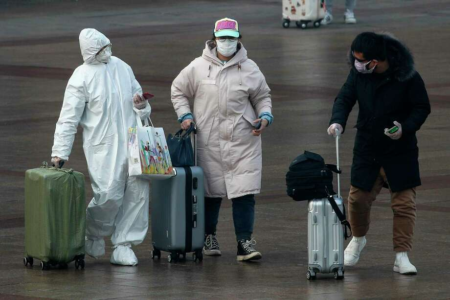 A passenger wearing a full-body protective suit catches the eyes of others as they walk out from the Beijing railway station in Beijing, Tuesday, Feb. 11, 2020. China's daily death toll from a new virus topped 100 for the first time and pushed the total past 1,000 dead, authorities said Tuesday after leader Xi Jinping visited a health center to rally public morale amid little sign the contagion is abating. (AP Photo/Andy Wong) Photo: Andy Wong / Associated Press / Copyright 2018 The Associated Press. All rights reserved