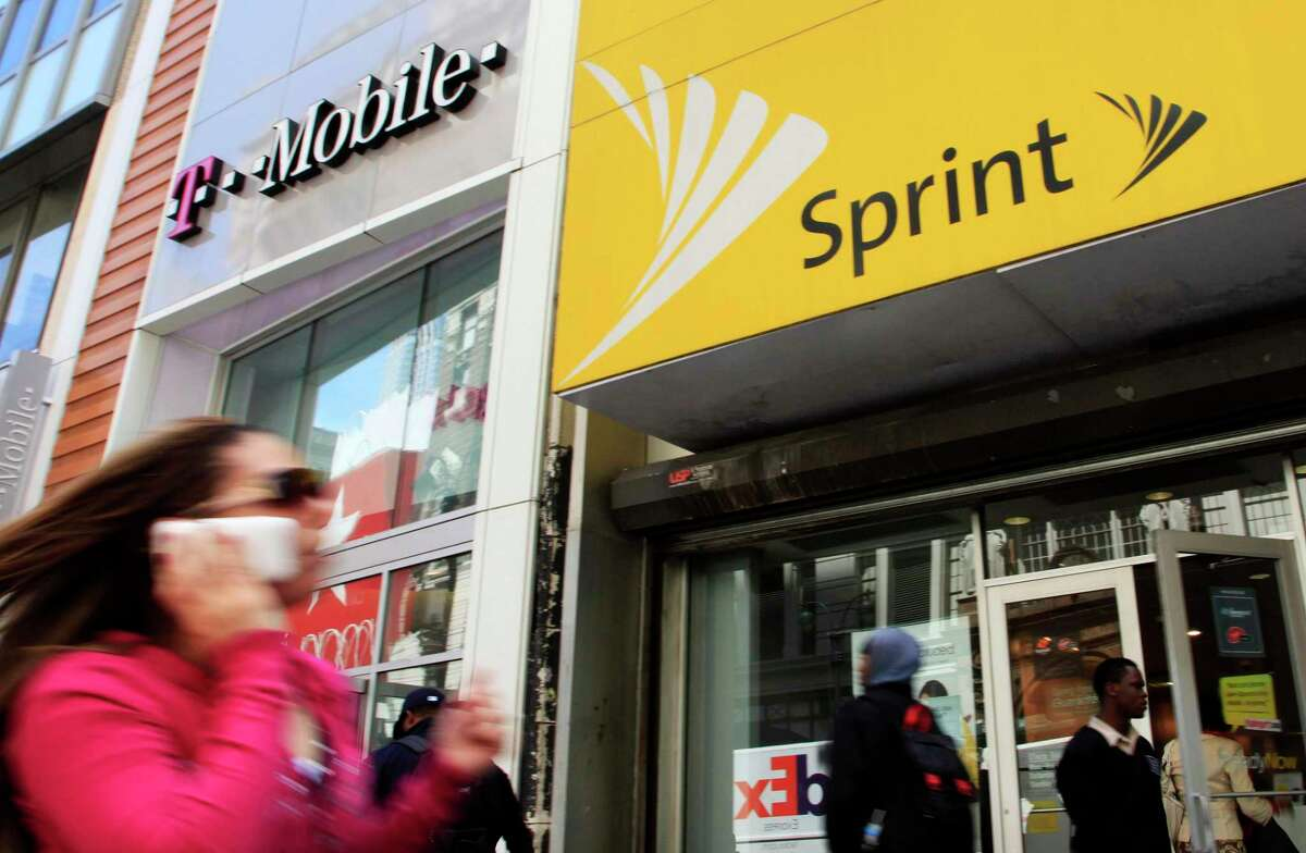 FILE - In this April 27, 2010 file photo, a woman using a cell phone walks past T-Mobile and Sprint stores in New York.