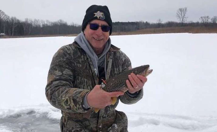 Tuscola County Sheriff Glen Skrent releases a $25,000 grand prize fish in Harmon Lake as part of the Fowler Center for Outdoor Learning's annual fundraiser ice-fishing contest. Per contest rules, the fish has to be released by a law enforcement officer. (Provided photo)