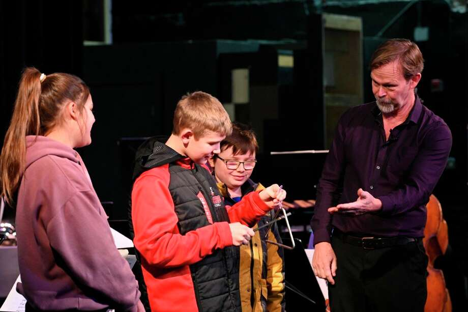 Robert Nordling invites students to help him demonstrate the sounds heard in an orchestra.