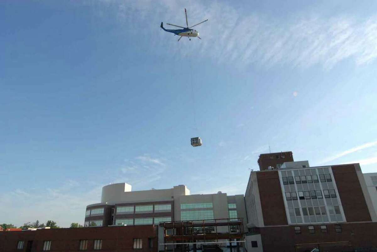 A construction helicopter lifts a large air-handling unit onto the roof of St. Peter's Hospital in Albany, New York 8/14/2010. ( Michael P. Farrell / Times Union )