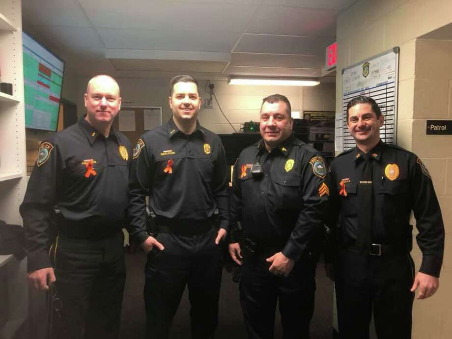Members of the Wilton Police Department are wearing orange ribbons in honor of Teen Dating Violence Awareness month in February. From left are Lt. Gregg Phillipson, Officer Rob Smaldone, Sgt. Anthony Cocco, and Capt. Rob Cipolla. Photo: Contributed Photo / Wilton Police Department / Wilton Bulletin Contributed