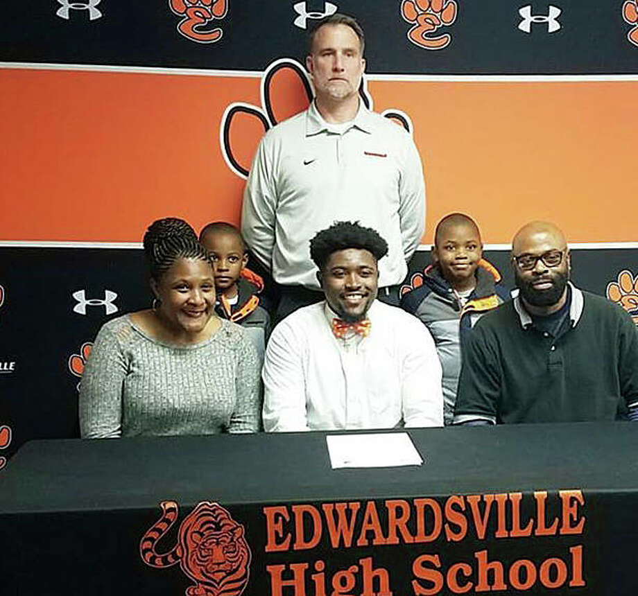 Edwardsville senior Trey Boyd, seated center, will play college football for Greenville University. He is pictured with his family and EHS coach Matt Martin.