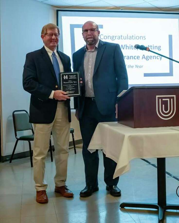 Jersey County Business Association Chair Tom Smith, left, presents Joe Heneghan of Heneghan, White, Cutting & Rice Insurance Agency with the group's Business of the Year Award on Feb. 6.