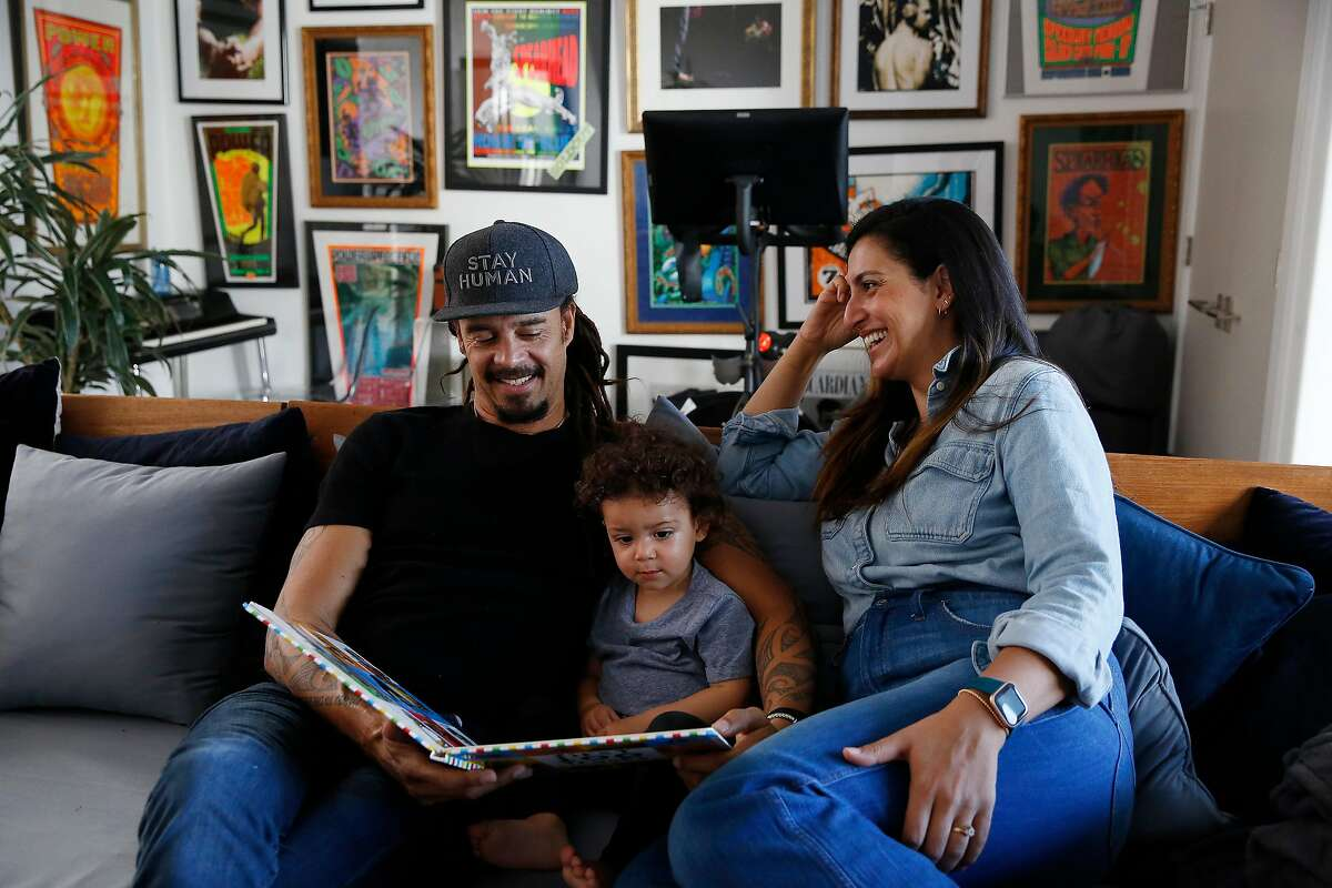 Michael Franti (left) looks at a picture book with his son Taj Franti (center), 17 months, as he talks with Sara Agah Franti (right) during an interview at their home on Monday, February 10, 2020 in San Francisco, Calif.