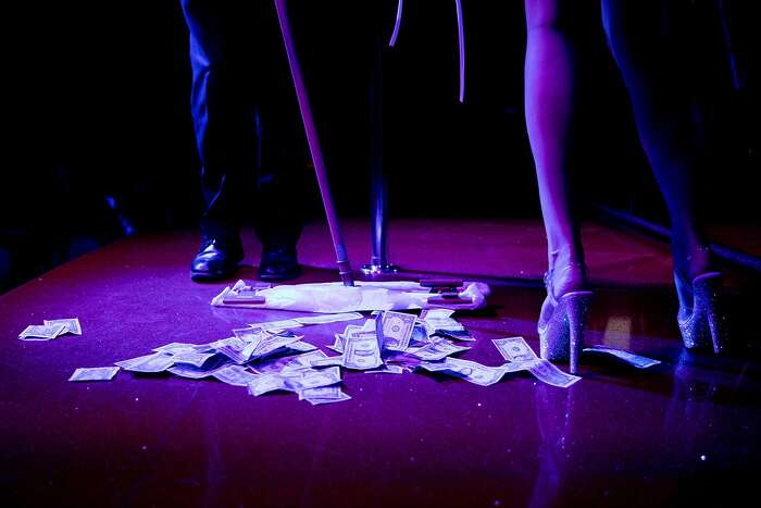 An attendant sweeps up tip money after Mia's performance on the main stage for patrons at the Condor Club in the North Beach neighborhood of San Francisco, Calif. Friday, February 7, 2020.