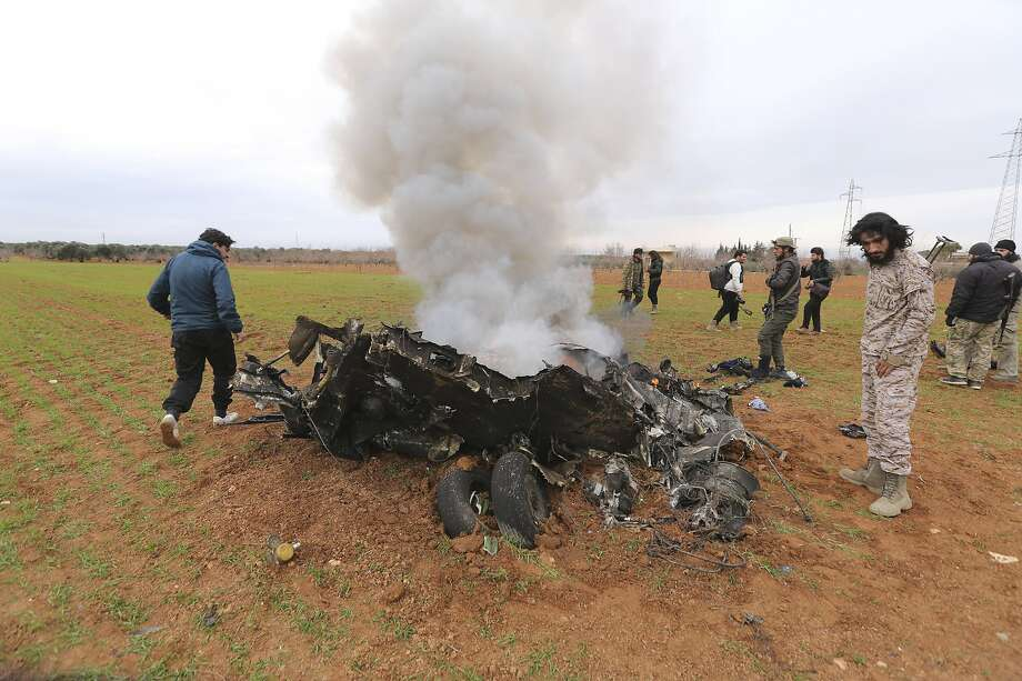 Insurgents look at a Syrian government helicopter that was shot down in the nation's last rebel stronghold in the northwest. Photo: Ghaith Alsayed / Associated Press