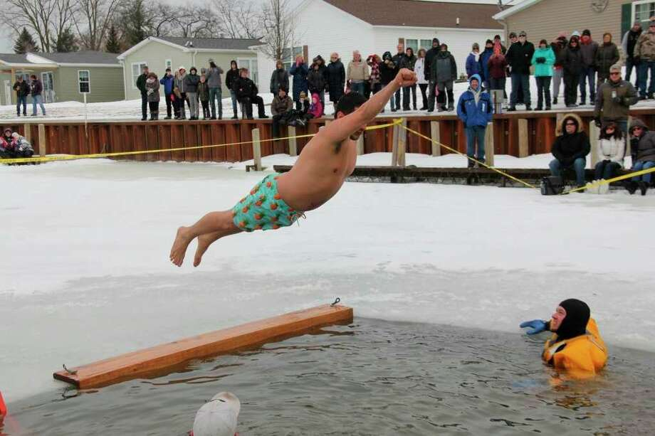 A diver jumps into the cold water at the Polar Bear Dip at 2019's Caseville Shanty Days. (Tribune file photo)