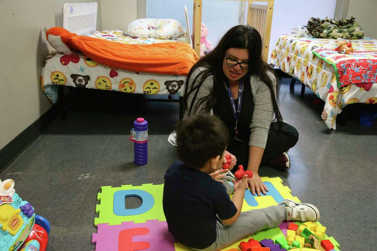 Intervention specialist Yolanda Luna works with a 2-year-old boy at the Whataburger Center, who has a genetic condition that requires a special diet. There aren't enough foster care homes in Bexar County to deal with medically complicated children, Sanchez said.