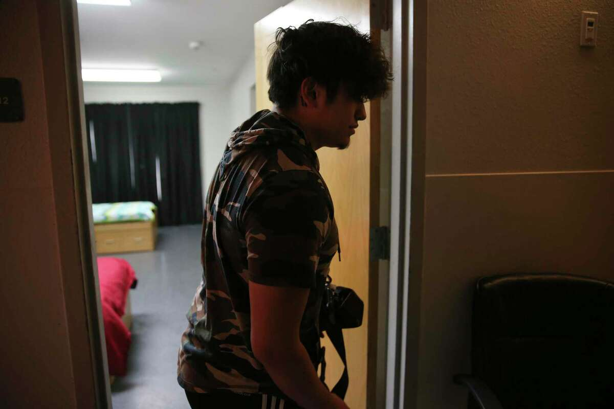 Intervention specialist Daniel Guerrero prepares a room for a client at the Whataburger Center, where the ratio of residents-to-staff is 2-to-1, owing to the need to provide more services to the kids who stay there.