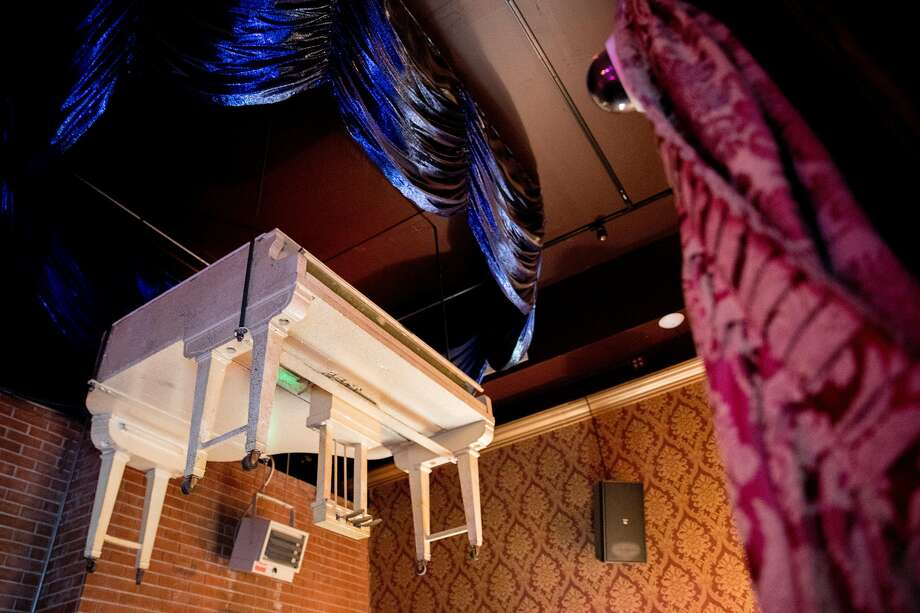 A large white piano used in performances during the early days of the Condor Club hangs from the ceiling. Famed dancer Carol Doda would descend from the piano to begin the evening's show, and in 1983, a man on the piano was killed when it was accidentally activated, crushing him into the ceiling. Photo: Jessica Christian / The Chronicle