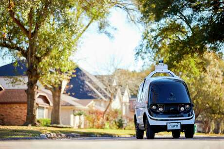 """The R2 self-driving delivery vehicle driving in Houston, Texas. Nuro said its R2 vehicle, designed to operate without any human driver, would be partnering with local businesses for """"last-mile delivery of consumer products, groceries, and hot food from local stores and restaurants."""""""