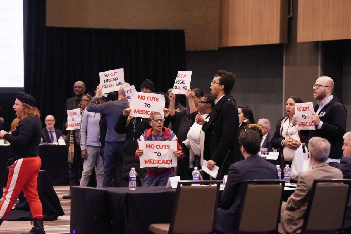 Protesters disrupt the first meeting of the Medicaid redesign team at the Albany Capital Center on Tuesday, Feb. 11, 2020, in Albany, N.Y. The protesters were ultimately escorted out of the meeting. (Paul Buckowski/Times Union)