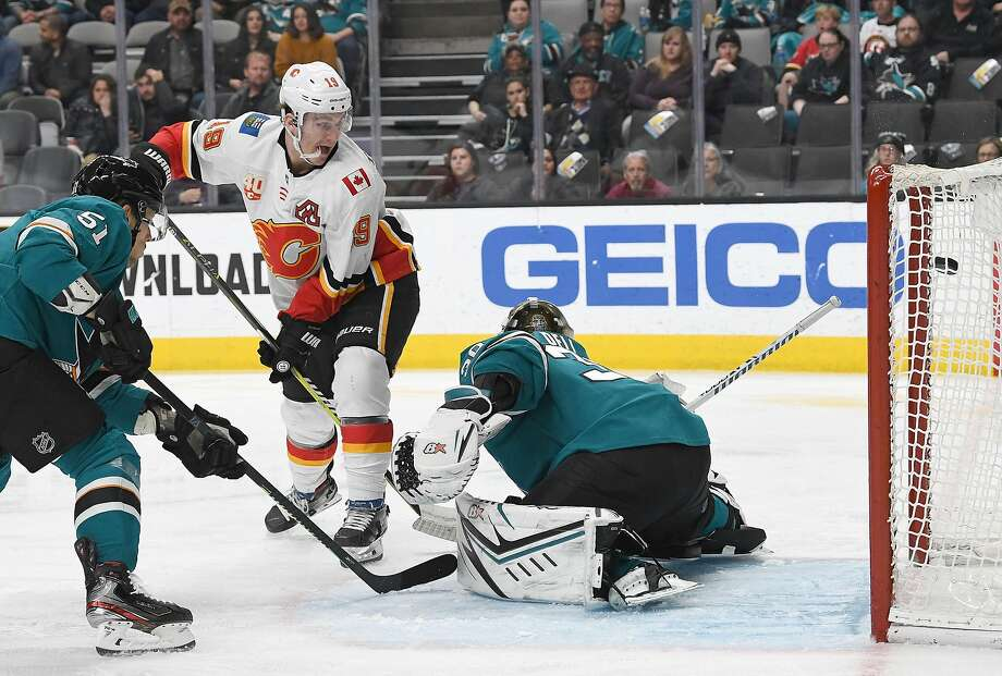 Calgary's Matthew Tkachuk puts the puck past Sharks' goalie Aaron Dell for a third-period goal in the Flames' 6-2 victory Monday night at SAP Center/ Photo: Thearon W. Henderson / Getty Images