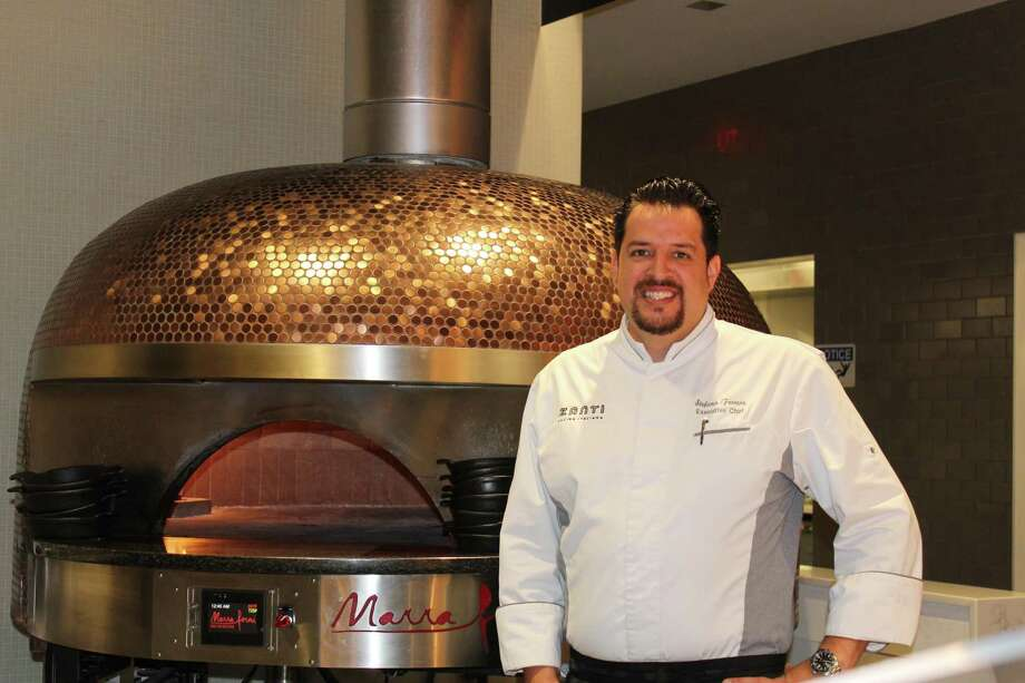 Chef Stefano Ferrero of Zanti Cucina Italiana poses next to their brick pizza over and at the bar of the classic Italian eatery on the far west side of The Woodlands. Ferrero came to the United States in 2017 after working many years in Mexico City and Italy. Photo: Photographs By Jeff Forward/The Villager / Photographs By Jeff Forward/The Villager