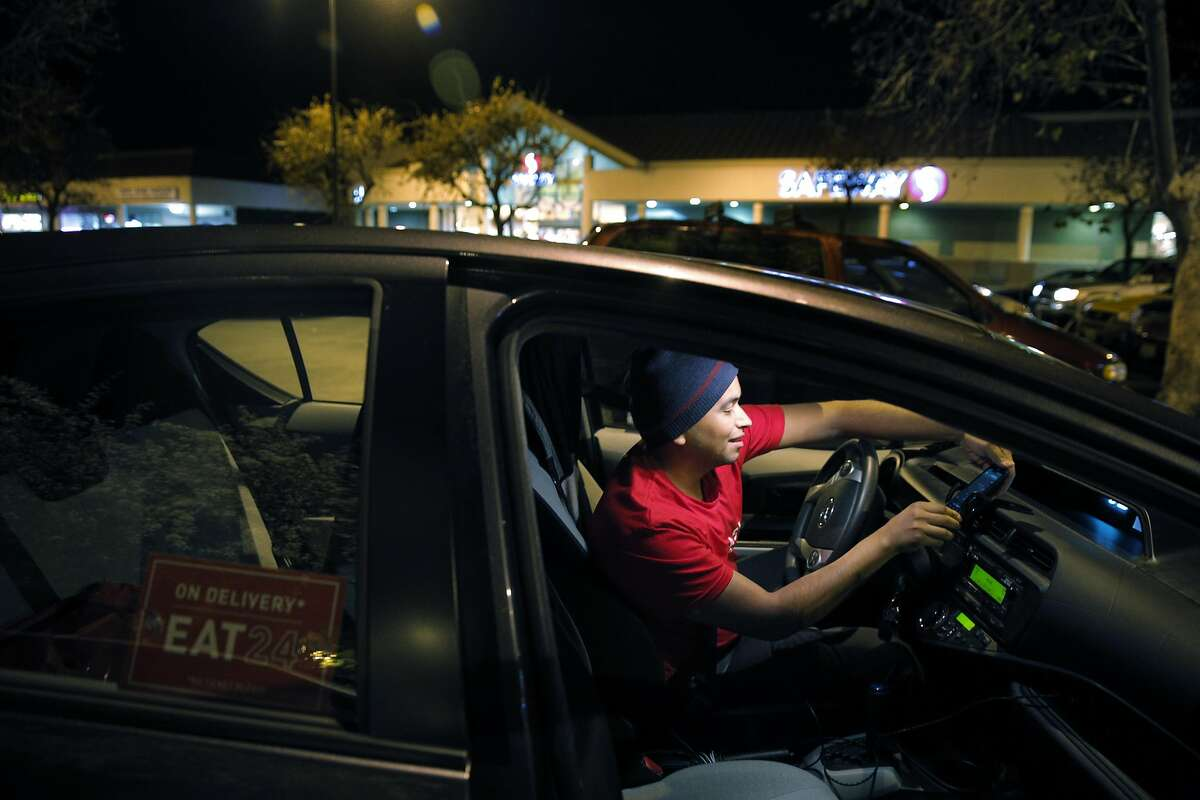 Eli Campos checks his phone for his next delivery in Campbell, Calif., on Tuesday, January 20, 2015. Eli drives for DoorDash, a food delivery service in addition to Lyft and Uber, and is glad to have the Intuit financial management software for self-employed people.