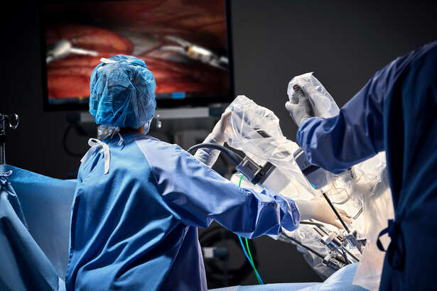Staff and physicians perform a spine procedure with the Intuitive Da Vinci Xi Robot.