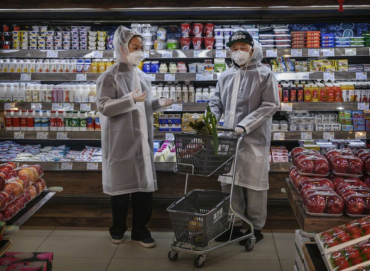 A Chinese couple wear plastic coats and protective masks as they shop for groceries at a supermarket on February 11, 2020 in Beijing, China. The number of cases of a deadly new coronavirus rose to more than 42000 in mainland China Tuesday, days after the World Health Organization (WHO) declared the outbreak a global public health emergency.