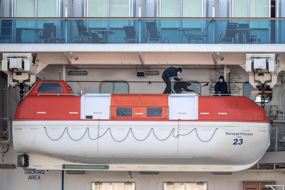 Crew members carry out maintenance on the Diamond Princess cruise ship in Yokohama on Tuesday. Misery abounds on the ship, as guests are quarantined and the number of coronavirus cases onboard has grown. Photo: Carl Court / Getty Images