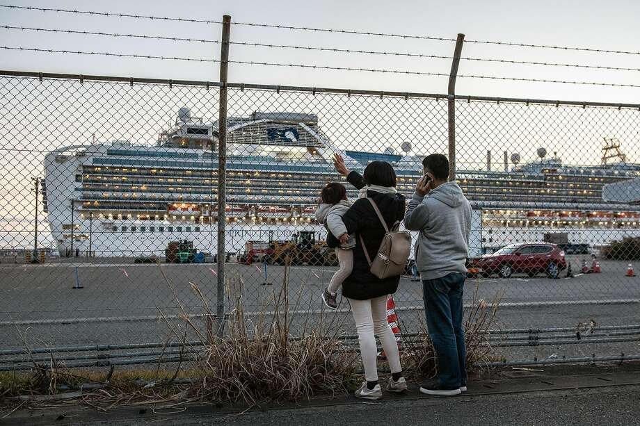 People wave to family on board the Diamond Princess cruise ship as it sits docked at Daikoku Pier in Yokohama. Well over 100 passengers on the ship are infected with the coronavirus. Photo: Carl Court / Getty Images