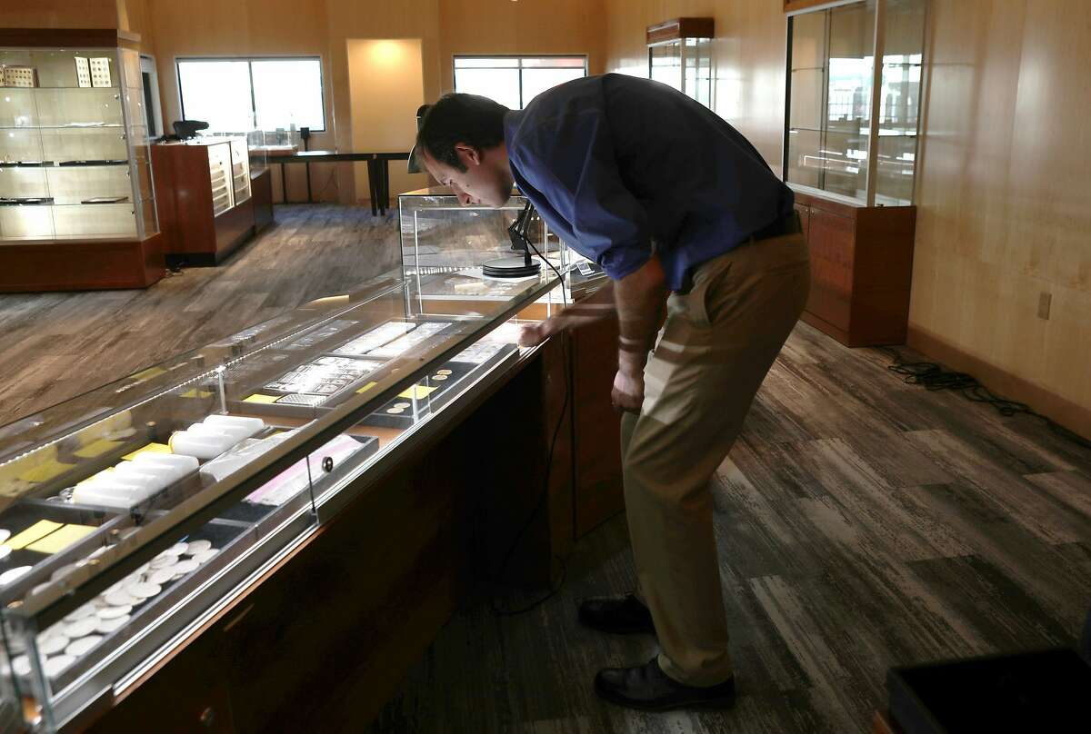 Sales manager James Andrews views coins at Witter Coins located in the old International House of Pancakes on Monday, Feb. 10, 2020, in San Francisco, Calif.